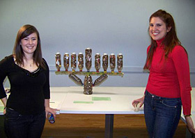From left: Emily Gwax and Jennifer Swan, students at the School of the Art Institute stand next to a submission by Gwax, Swan and Emily Boksenbaum, also an Art Institute student. The menorah is constructed in part from recycled plastic bottles. The piece also functions as a compost container, which will be emptied after Chanukah and used for a garden.