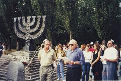 Goldman stands in front of a large public menorah
