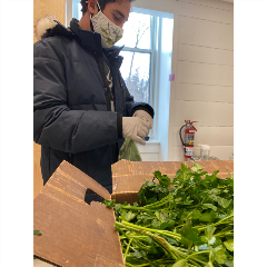 A student in a mask stands in front of a box of greens