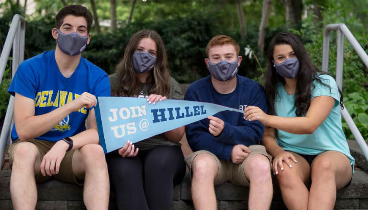 Four students wearing masks holding a sign that says join us at Hillel.