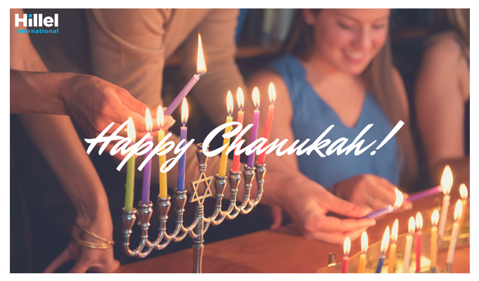 "Text reads ""Happy Chanukah"" with an image of students lighting Menorahs."