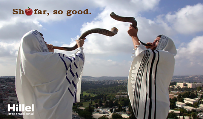 """Shofar, so good."" Image of two men in tallits blowing shofars with the Jerusalem skyline in the background"