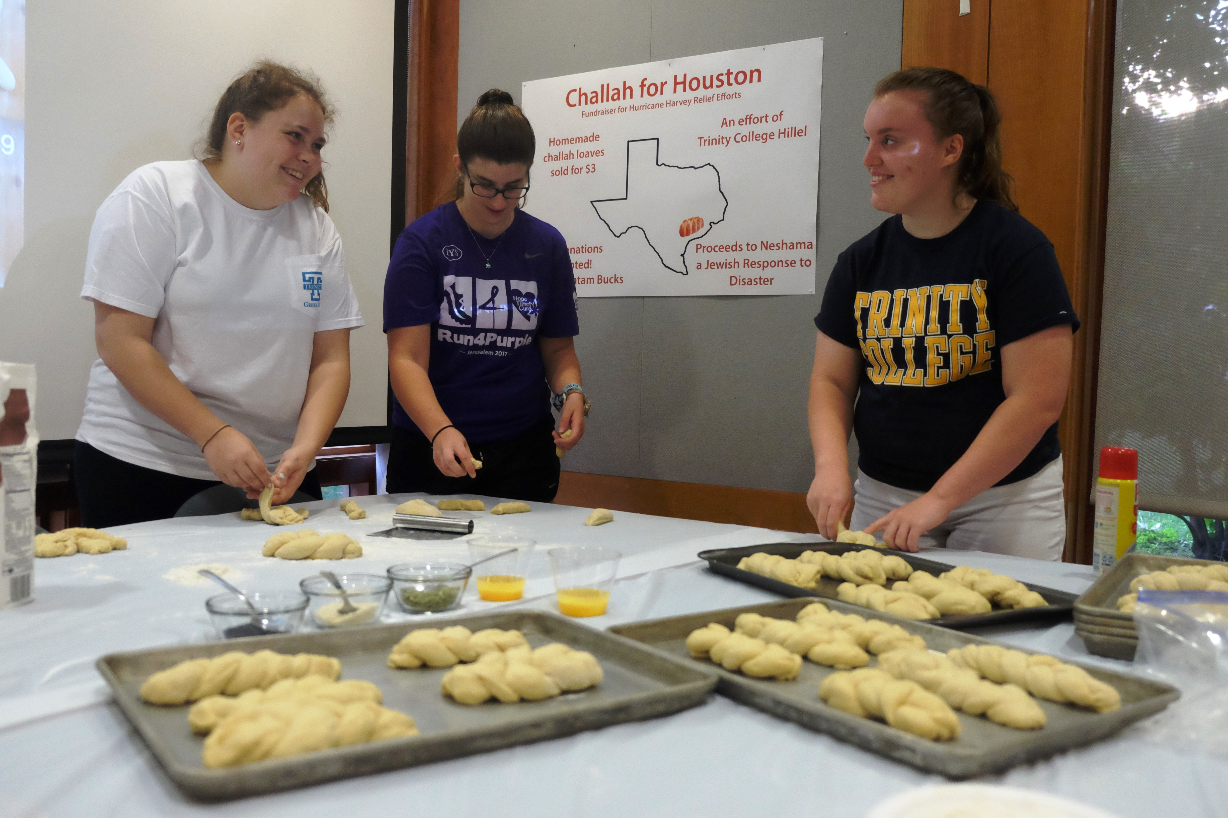 Students stand at a table with trays of challah.