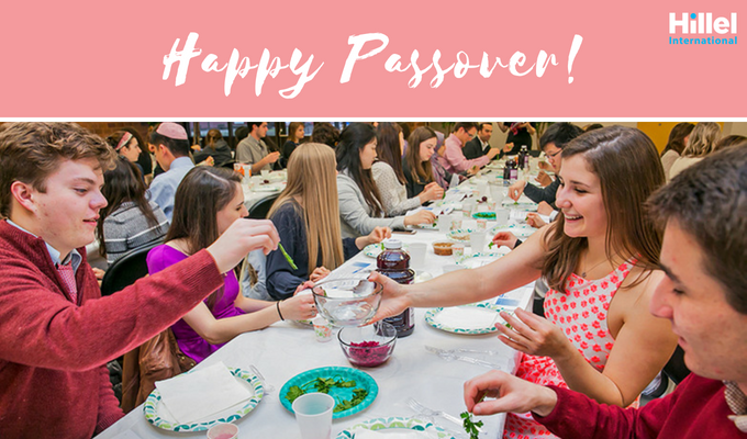 Happy Passover message on pink background with Students eating at a Seder.