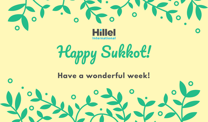 """Happy Sukkot, Have a Wonderful Week!"" written on a yellow background with tree branches and leaves on the border."