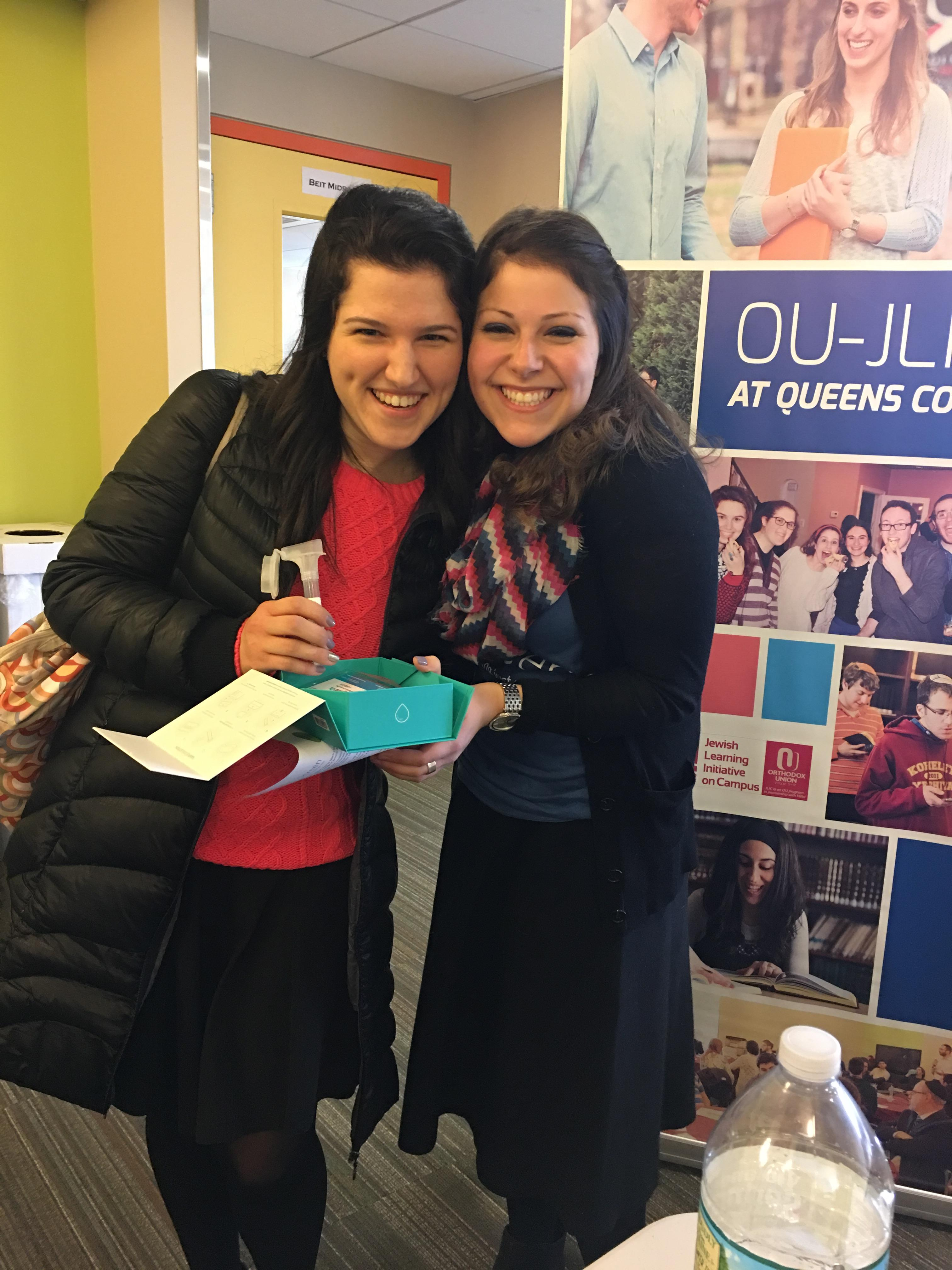 Two women with brown hair smile at the camera during a screening event at Queens College.