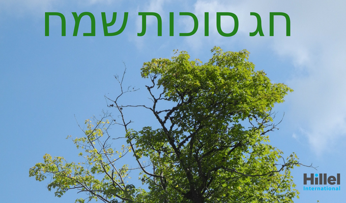 Hag Sukkot Sameach written in Hebrew in green text with a tree in the background