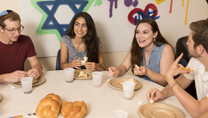 Four students laughing and smiling as they share a shabbat meal together.